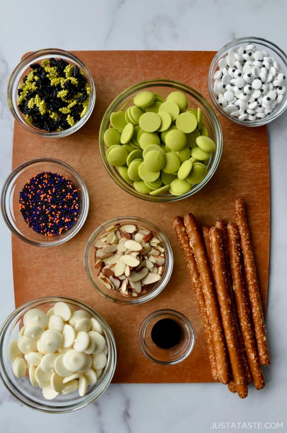A cutting board containing glass bowls with ingredients for making chocolate pretzels