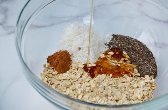 A glass bowl containing oats, coconut, spices and honey