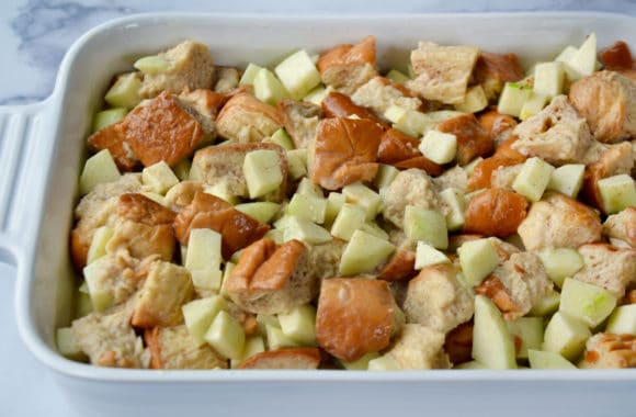 White baking dish containing unbaked apple bread pudding