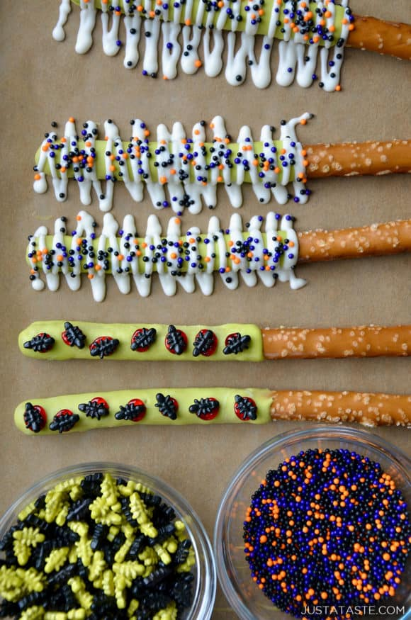 Brown parchment paper topped with bowls of Halloween sprinkles and pretzel rods