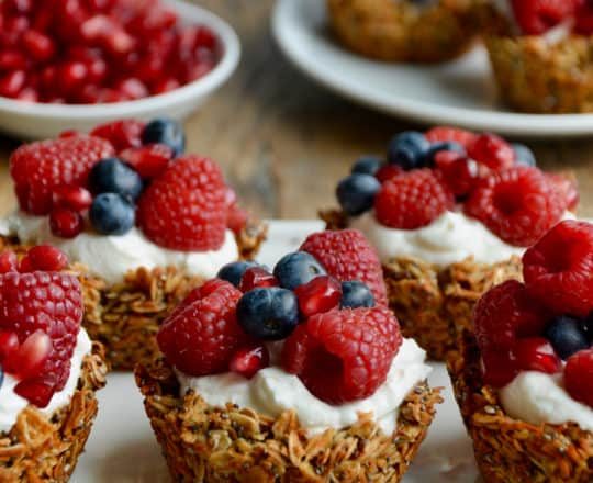 Muffin Tin Granola Cups topped with yogurt and fresh fruit