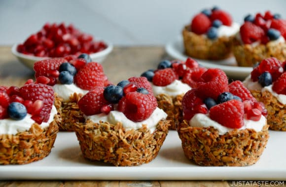 Easy Muffin Tin Granola Cups topped with yogurt and fresh berries on white serving plate