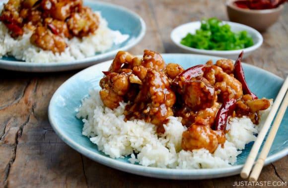 Blue plate containing Homemade General Tso's Cauliflower, white rice and chopsticks