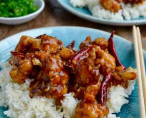 Easy General Tso's Cauliflower over white rice on blue plate with chopsticks