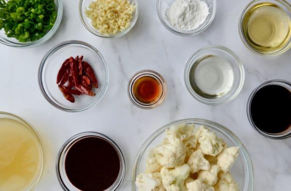 Various sized glass bowls containing chopped scallions, minced ginger, cornstarch, vegetable oil, hoisin sauce, sesame oil, rice wine vinegar, vegetable stock and cauliflower florets