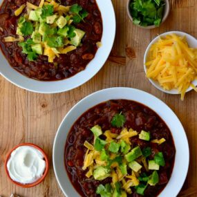 Two white bowls filled with chili and smaller bowls surrounding them containing chili toppings
