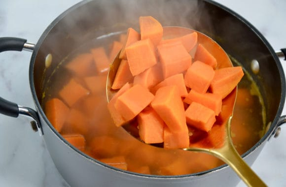 Metal spoon containing diced yams over large stockpot