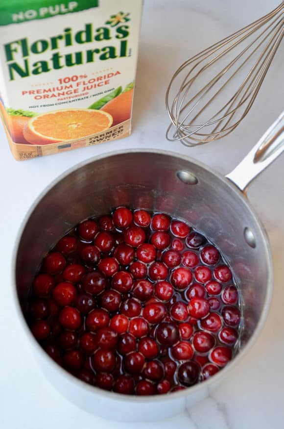 A saucepot filled with cranberries and orange juice