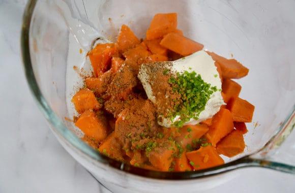 Tigela de vidro contendo batatas em cubos, cream cheese, cebolinha fresca e especiarias
