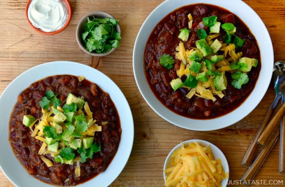Two bowls of chili surrounded by cilantro, cheese and sour cream