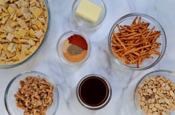 A variety of different sized bowls containing Chex Mix cereal, butter, spices, pretzels, walnuts, peanuts and Worcestershire sauce