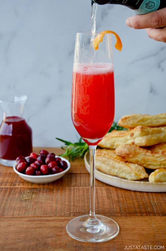 Cranberry Champagne Cocktail in Champagne flute with orange twist and fresh cranberries and pastries in the background