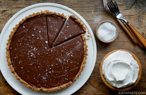 Chocolate-Peanut Butter Pretzel Tart next to bowls containing whipped cream and sea salt