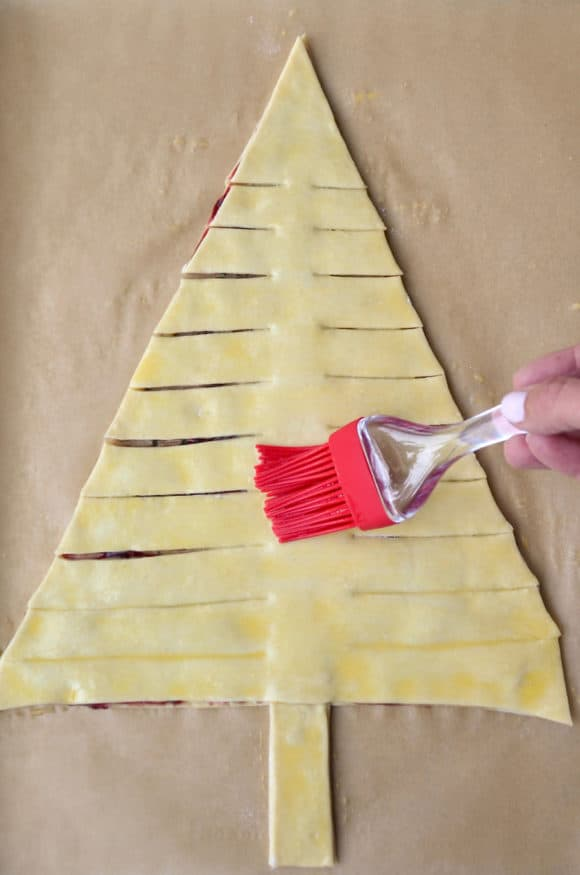 Brushing egg wash atop holiday puff pastry appetizer