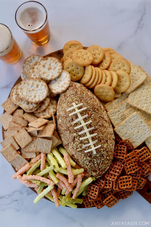 A wood board with a football cheese ball and snack foods surrounding it