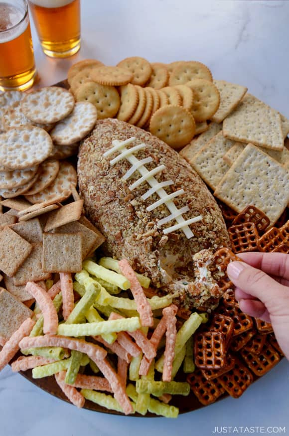 A pretzel being dipped into a cheese ball with snacks surrounding it