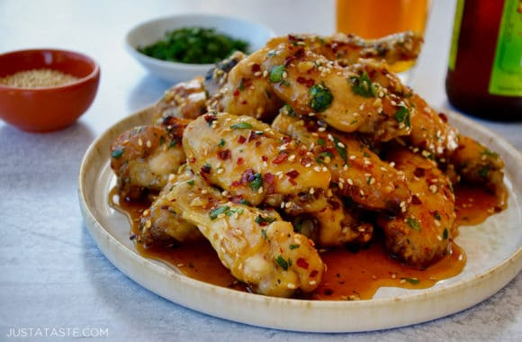 A plate containing chicken wings with cilantro and sesame seeds
