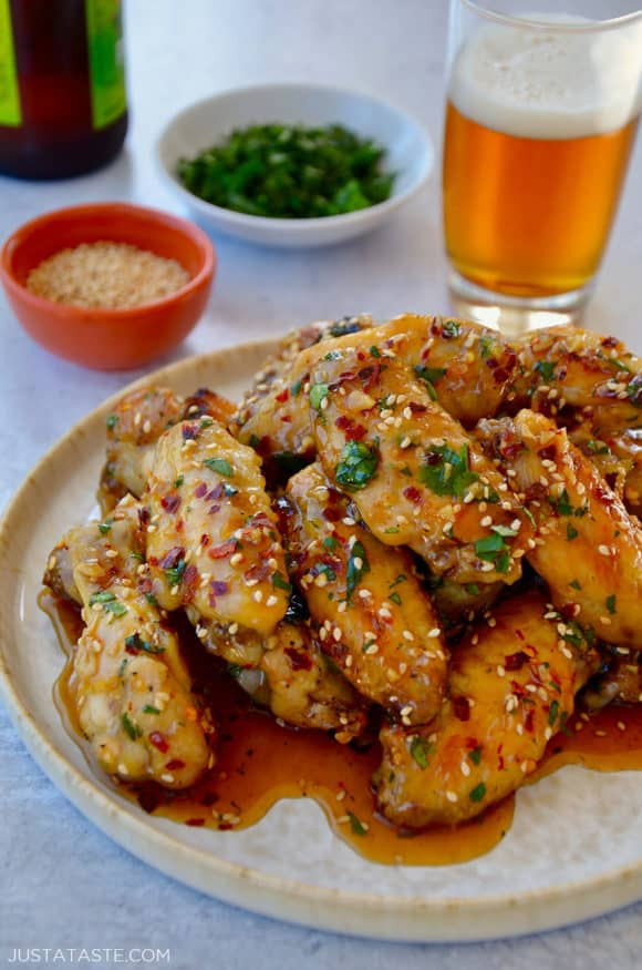 A white plate containing chicken wings with sesame seeds, cilantro and a beer in the background