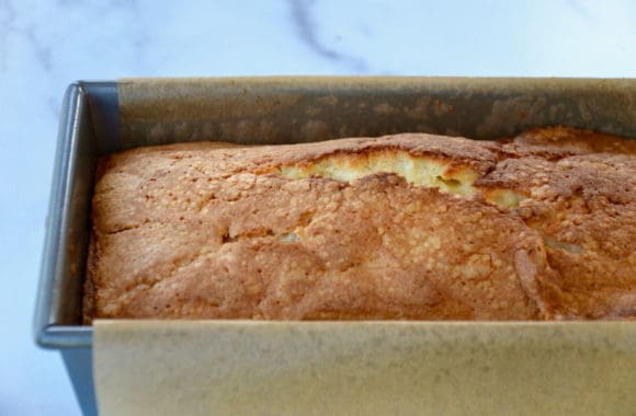 Parchment paper lined loaf pan containing freshly baked cake