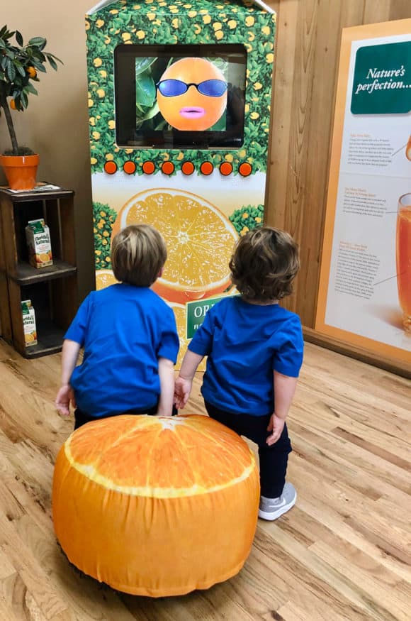 Two toddler boys sitting on an orange pillow watching a TV screen
