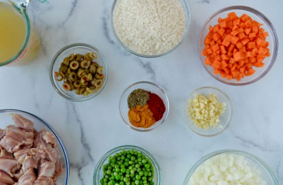 Various sized bowls containing chicken stock, green olives, diced onions and carrots, minced garlic, spices, frozen peas, basmati rice and uncooked cubed chicken thighs