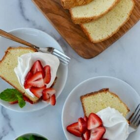 Cream Cheese Pound Cake sliced on cutting board with two slices on dessert plates with whipped cream and fresh strawberries