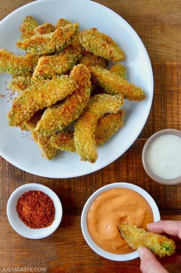 Hand dipping avocado fry into aioli sauce next to plate containing Crispy Baked Avocado Fries and small ramekins with spices and ranch
