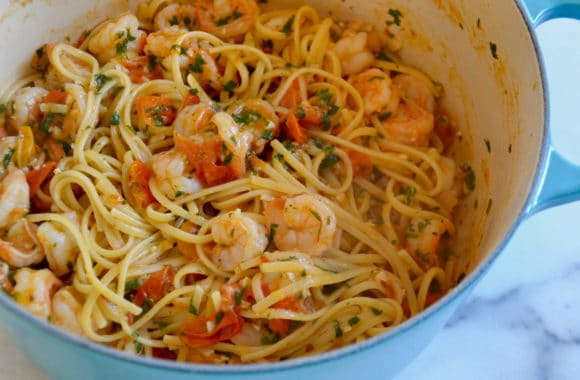 Large pot containing linguine pasta, shrimp, cherry tomatoes, parsley and garlic