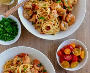 Two bowls with Quick Shrimp Scampi next to a glass of wine and small bowls containing cherry tomatoes, chili flakes and parsley