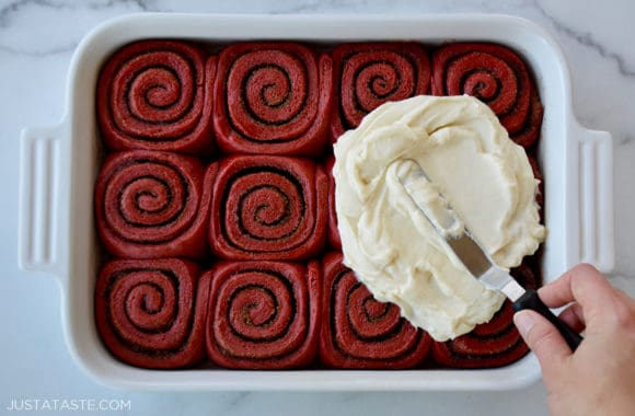 A white baking dish with red velvet cinnamon rolls and a spatula slathering cream cheese frosting on top