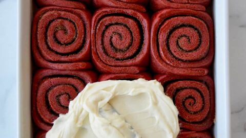 A white baking pan with red velvet cinnamon rolls and cream cheese frosting being slathered on top