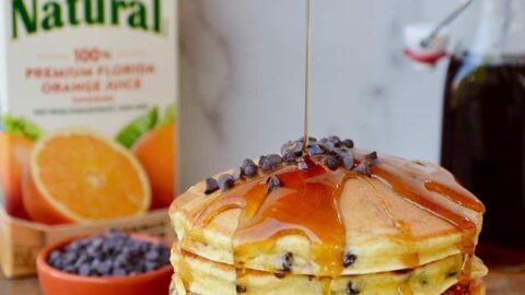 Stack of pancakes on a white plate with a carton of orange juice behind it