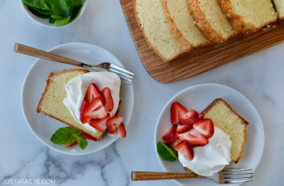 Two dessert plates with a slice of Cream Cheese Pound Cake topped with whipped cream, fresh mint leaves and sliced strawberries next to cutting board with more slices of cake
