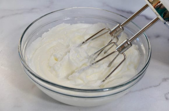 Egg whites being whipped with a handheld beater in a glass bowl