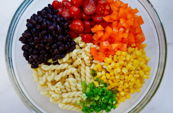 Glass bowl containing diced tomatoes, diced orange bell pepper, yellow corn kernels, sliced scallions, cavatappi and black beans