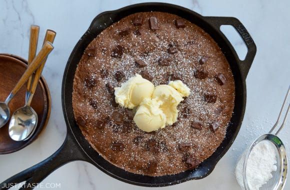 A cast-iron skillet brownie topped with vanilla ice cream