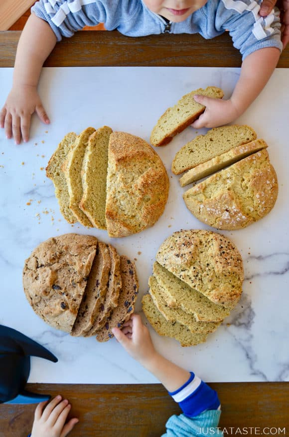 Little boys reaching for sliced loaves of bread on a table