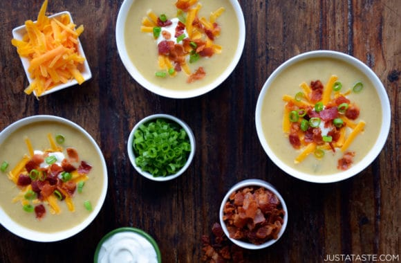 Loaded baked potato soup in bowls topped with crispy bacon, cheddar cheese, sour cream and scallions