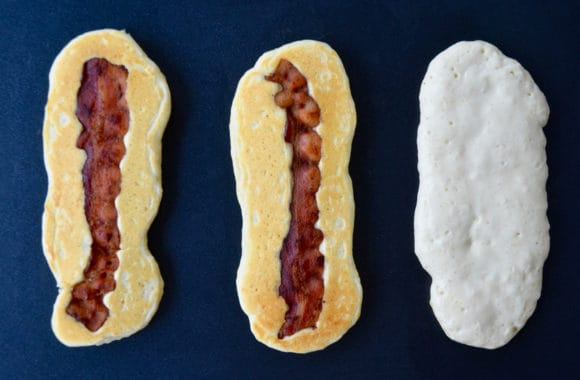 Griddle containing three pancake dippers with bacon