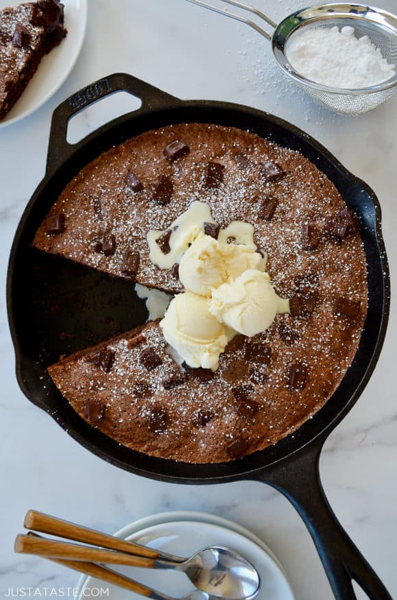 A cast-iron skillet brownie topped with ice cream and confectioners' sugar