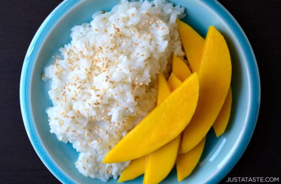 Thai Coconut Sticky Rice with sliced mango on blue plate