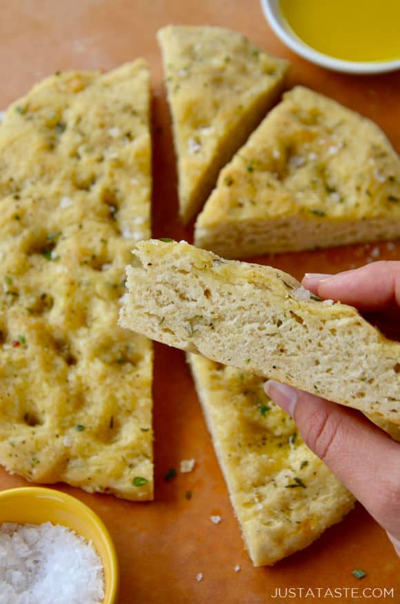 Hand holding a slice of no-yeast focaccia bread