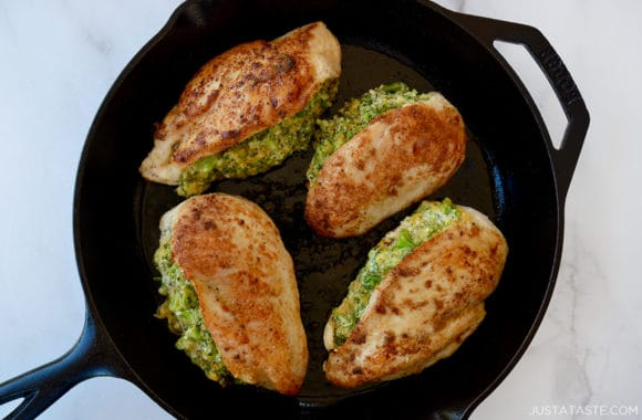 A cast-iron skillet containing seared, stuffed chicken breasts