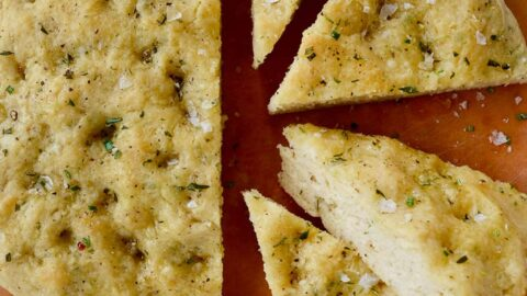 Four slices of Easy Homemade Focaccia (No Yeast) next to small bowls containing kosher salt and olive oil