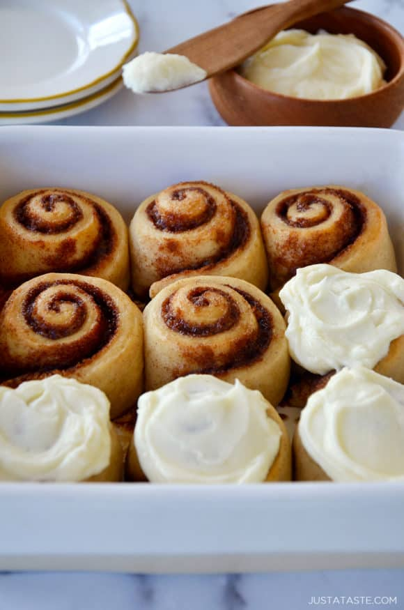 A white baking dish with cinnamon rolls and a bowl of frosting