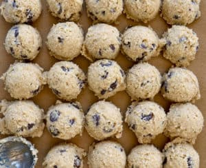 Rows of small scoops of edible cookie dough on brown parchment paper