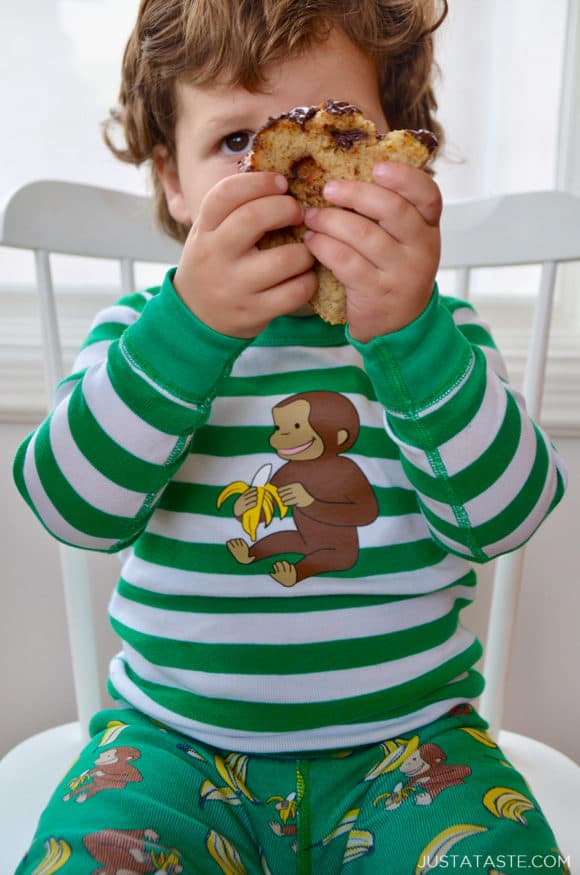 Child on chair holding a slice of banana bread up to his face