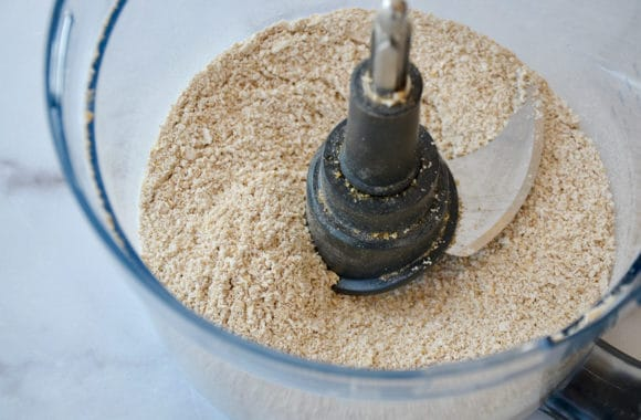 A food processor bowl containing oat flour