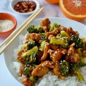 Quick Orange Chicken and Broccoli over white rice in bowl with chopsticks next to a sliced orange