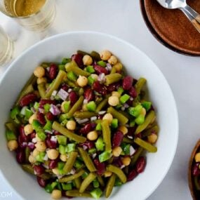 A white bowl with bean salad and plates next to it